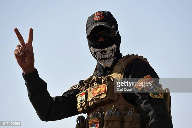 An Iraqi soldier gives a V sign during the offensive to recapture the city of Mosul from Islamic State militants on October 23 2016 in Bartella Iraq...