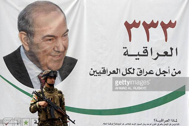 An Iraqi soldier guarding a location of alIriqayah secular bloc stands in front of a portrait of former Iraqi premier Iyad Allawi in Baghdad on April...