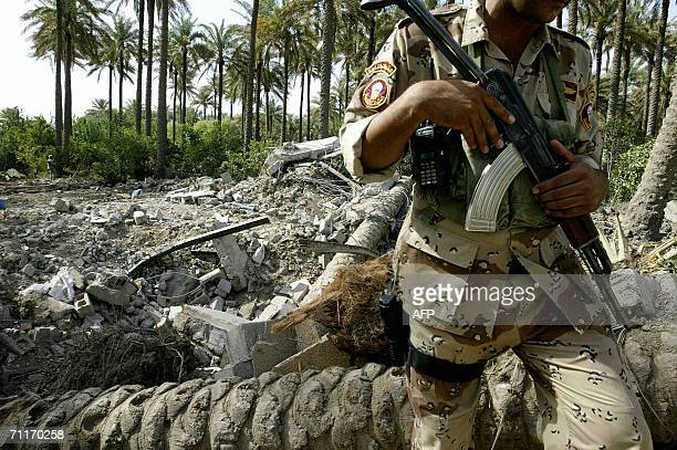 An Iraqi soldier guards the scene of the recent airstrike against alQaeda leader in Iraq Abu Musab alZarqawi in an isolated palm grove on the...
