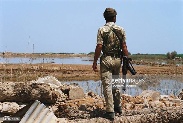 An Iraqi soldier holding an AK47 rifle surveys the marshes of the Fao Peniunsula during the war when Iraq recaptured the peninsula from Iran