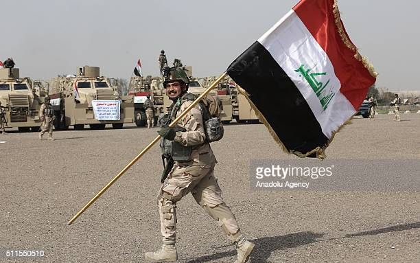 An Iraqi soldier holds flag of Iraq before going to Mahmur district of Mosul to attend an operation aiming retake the city from ISIS on February 21...