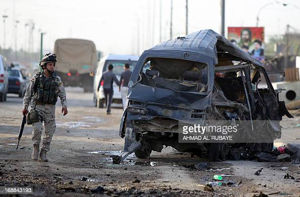 An Iraqi soldier inpects the remains of a vehicle at the scene of a car bomb explosion the previous days in Baghdad's Sadr City district on May 16...