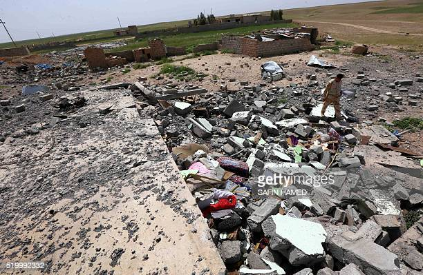 An Iraqi soldier inspects the rubble of a collapsed building as he secures an area near the frontline on April 9 2016 in the town of Kharbardan...