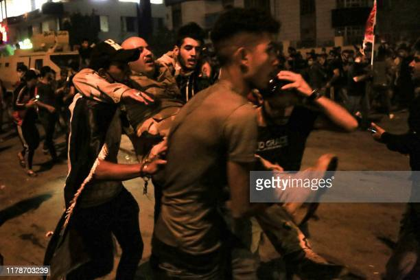 An Iraqi soldier is carried away by demonstrators during anti-government protests in the Shiite shrine city of Karbala, south of Iraq's capital...