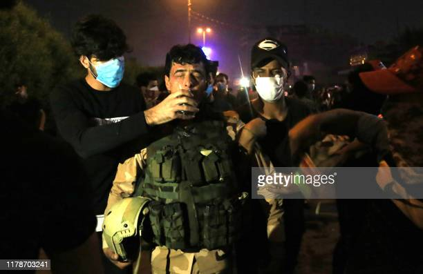 An Iraqi soldier is comforted by demonstrators during anti-government protests in the Shiite shrine city of Karbala, south of Iraq's capital Baghdad,...