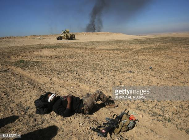 TOPSHOT An Iraqi soldier lies on the ground awaiting to be evacuated after he was wounded in an explosivesladen vehicle attack claimed by Islamic...