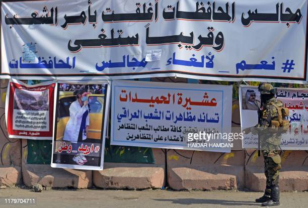 "An Iraqi soldier looks at a banner reading ""Provincial councils were closed by order of the people and will soon be abolished"" hung on Diwaniyah's..."