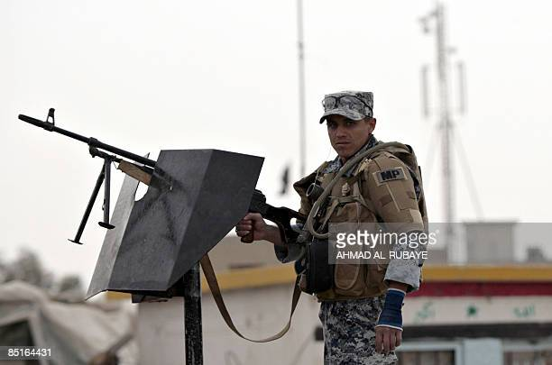 An Iraqi soldier mans his gun as he and US soldiers secure a street waiting for the arrival a shipment of sports clothes donated from the USA for...