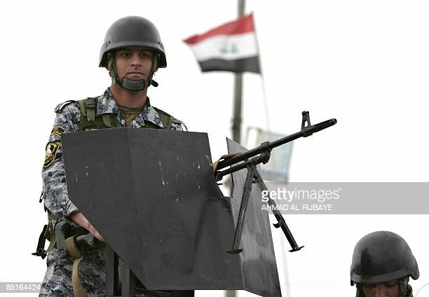 An Iraqi soldier mans his gun as they and US soldiers secure a street waiting for the arrival a shipment of sports clothes donated from the USA for...
