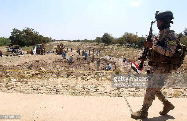 An Iraqi soldier marches at the site of a mass grave containing the remains of people believed to have been slain by jihadists of the Islamic State...