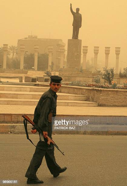 An Iraqi soldier passes a statue of President Saddam Hussein in alFardous street as a sandstorm blows over Baghdad 25 March 2003 USled bombing in the...
