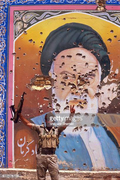 An Iraqi soldier poses with an AK47 in one hand and his other hand giving a victory sign in front of a mural The mural damaged by gunfire depicts...