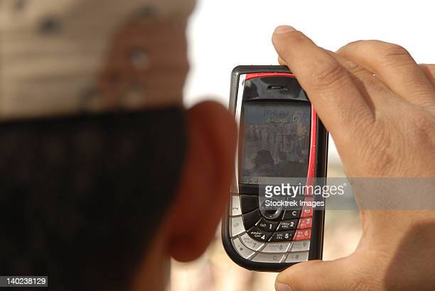 An Iraqi soldier records a change of command ceremony with his cell phone.
