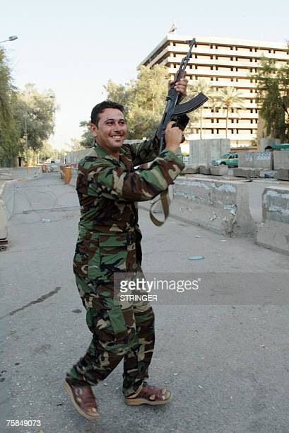 An Iraqi soldier shoots in the air as he celebrates the victory of his country's football team against Saudi Arabia for the final of the Asian...