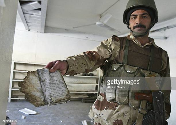 An Iraqi soldier shows a burned prayer book inside a damaged Sunni mosque which was bombed early morning on February 28 2006 in Baghdad Iraq...