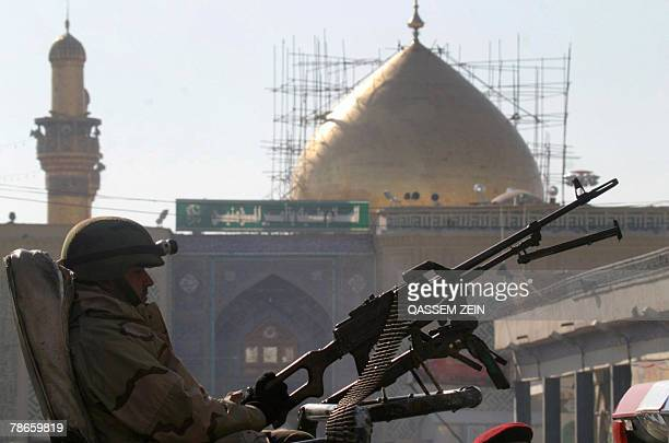 An Iraqi soldier sits behind a machine gun in front of the entrance to the Imam Ali Shrine in Najaf 160 kms south of Baghdad 27 December 2007 on the...