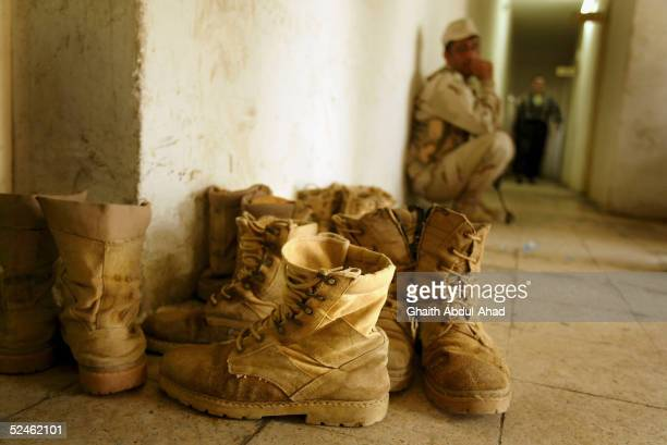 An Iraqi soldier sits near a pile of soldiers boots on March 4, 2005 in the restive northern city of Mosul, Iraq. Building a strong Iraqi security...