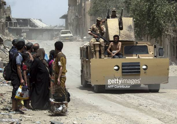 An Iraqi soldier sits on a tank with a man alleged to be an Islamic State group member as civilians flee the Old City of Mosul on July 3 during the...
