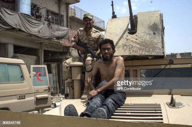 An Iraqi soldier sits on a tank with a man alleged to be an Islamic State group member in the Old City of Mosul on July 3 during the government...