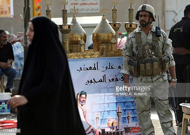 An Iraqi soldier stands guard as Shiite Muslim pilgrims make their way on foot to the AlKadhimiya district of the Iraqi capital Baghdad to...