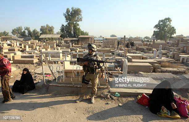 An Iraqi soldier stands guard as Sunni Muslims visit the graves of loved ones at the AlGhazali cemetery in Baghdad on November 16 2010 on the first...