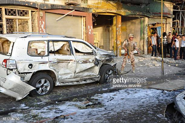 An Iraqi soldier stands guard at the site of a car bomb explosion in a Kurdishmajority neighbourhood of the ethnically mixed northern city of Kirkuk...