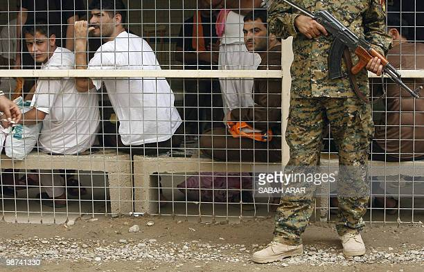 An Iraqi soldier stands guard in front of prisoners waiting to be released from AlRusafa detention facility in Baghdad on April 29 2010 About 120...