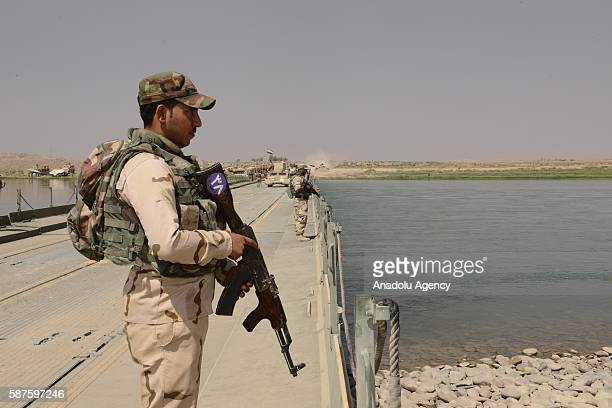 An Iraqi soldier stands guard on the temporarily constructed bridge will be used to dispatch military deliveries on Tigris River dispatching to Al...