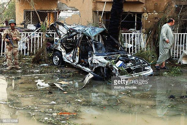 An Iraqi soldier stands near a destroyed car as he secures the area where two suicide car bombs exploded near an Interior Ministry building on...