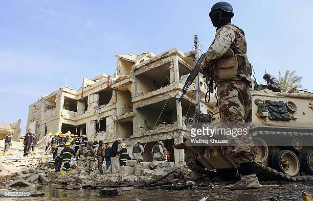 An Iraqi soldier stands near a US Bradley armoured vehicle as they secure the area where two suicide car bombs exploded near an Interior Ministry...