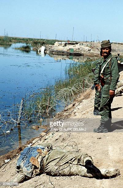 An Iraqi soldier stands near the corpses of Iranian soldiers laying in the swamp near the Iraqi city of alHoweizah north of Basra on March 20 1985...