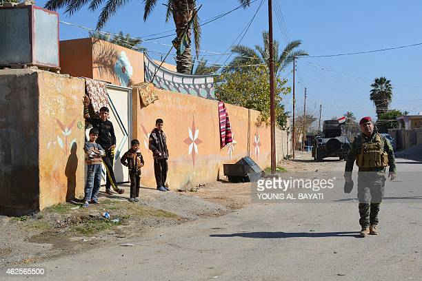 An Iraqi soldier walks in a street during a visit with officials in the village of Brawna outside the town of Muqdadiyah in the Diyala province on...
