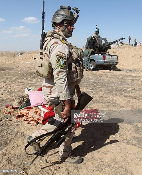An Iraqi soldier walks in an army gathering area on April 14 2015 in the Garma district west of the Iraqi capital Baghdad where progovernment forces...