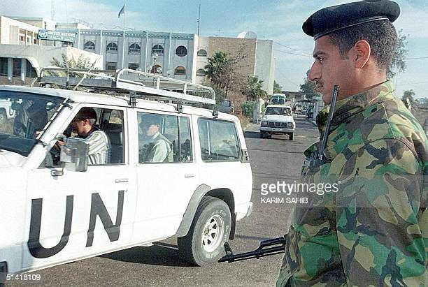 An Iraqi soldier watches as members of the UN weapons inspections team in Baghdad leave headquarters for their daily work 10 December one day after...