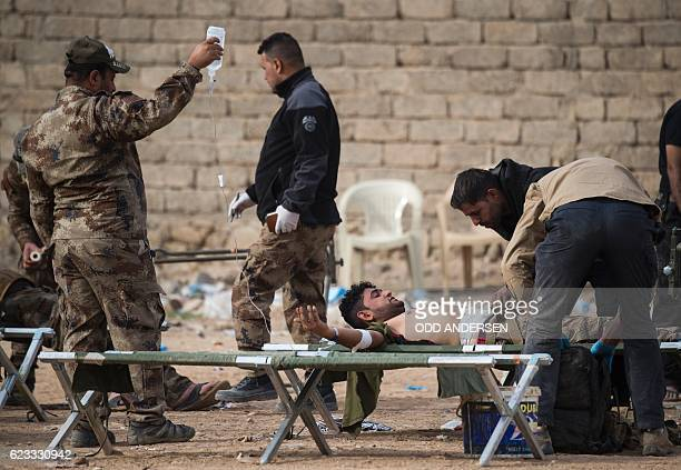 An Iraqi soldier with shrapnel wounds to his abdomen receives treatment at an Iraqi Special Forces 2nd division outdoor field clinic in the Samah...