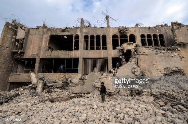 An Iraqi stands on the rubble of the destroyed seven-storey Chadirji Building, designed by celebrated Iraqi architect Rifat Chadirji in the 1960s, on...