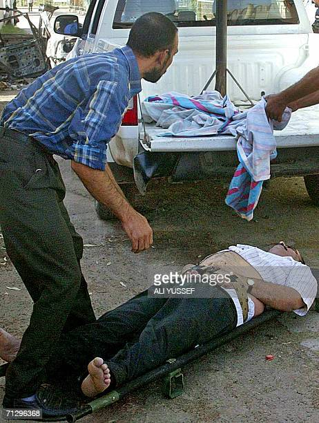 An Iraqi stands over his dead colleague at the entrance of a hospital 26 June 2006 in the restive city of Baquba northeast of Baghdad Seven Iraqis...