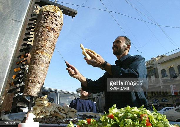 An Iraqi street vendor prepares a Shawarma sandwich as two Muslim children wait for it 24 November 2003 in Baghdad Iraq's Sunnis and Libyans on...