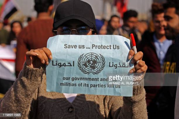 An Iraqi student lifts a placard during an antigovernment demonstration in the capital Baghdad's Tahrir square on February 6 after a night of...