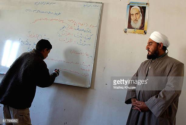 An Iraqi Sunni cleric teaches a religious lesson while standing near an image of Hamas founder Shekh Ahmad Yassin at Sheikh Maroof Sunni School...