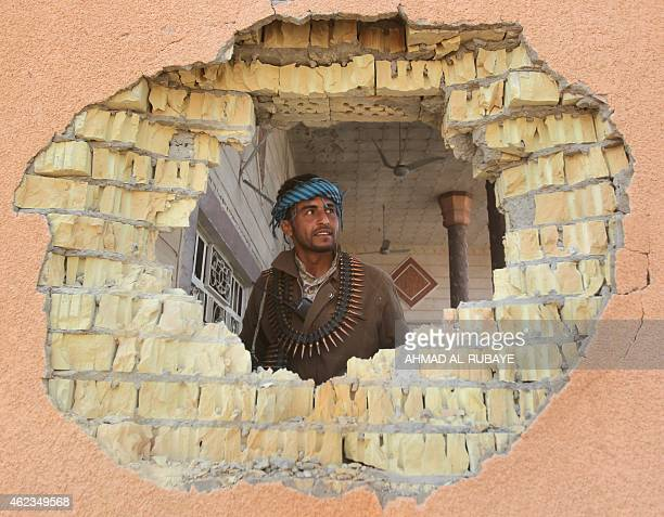 An Iraqi Sunni fighter checks house that was damaged during clashes against Islamic State group fighters in the village of Sharween in Diyala...