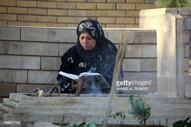An Iraqi Sunni Muslim woman reads from the Koran as she visits the graves of loved ones at the AlGhazali cemetery in Baghdad on November 16 2010 on...