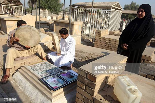 An Iraqi Sunni Muslim woman visits the graves of her four children who were killed in a bomb blast at the AlGhazali cemetery in Baghdad on November...