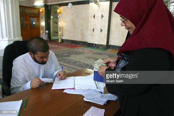 An Iraqi Sunni woman registers her name to vote on the 15th of October referendum on Iraqs new constitution August 27 2005 at a Sunni mosque in...