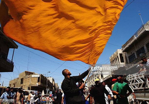 An Iraqi supporter of radical Iraqi Shiite cleric Moqtada al-Sadr waves a religious flag as he takes part in a protest against the visit of U.S...
