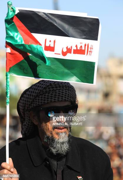 An Iraqi supporter of Shiite cleric Moqtada alSadr holds up a Palesetinian flag with the Arabic slogan 'Jerusalem is ours' during a protest that...
