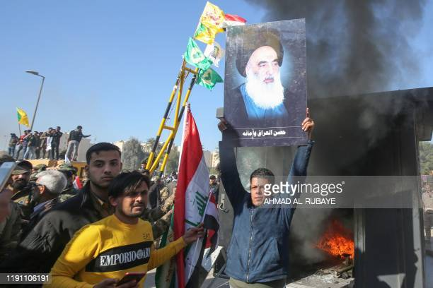 An Iraqi supporter of the Hashed al-Shaabi military network lifts a picture of Iraq's top Shiite cleric Grand Ayatollah Ali Sistani during a rally in...
