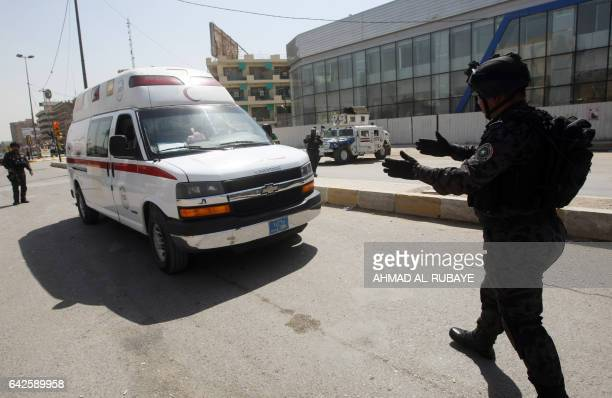 An Iraqi SWAT team member guides an ambulance on a street leading to the heavily fortified Green Zone in Baghdad on March 23 2012 Iraq tightened...