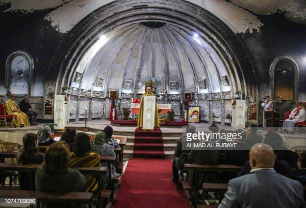 An Iraqi Syriac Catholic priest leads Christmas morning mass at the Mar Behnam and Mart Sarah Syriac Catholic Church which was damaged and defaced...