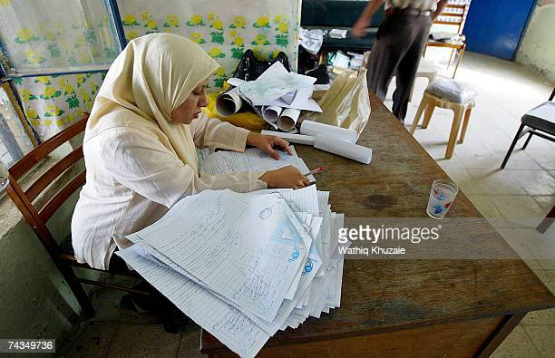 An Iraqi teacher looks into exam papers on May 29 2007 in a school in the Sadr city neighborhood of Baghdad Iraq The United Nations International...